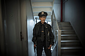Portrait of older Caucasian policewoman holding gun in apartment staircase