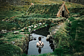 Caucasian woman swimming in pond near rural house