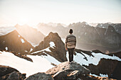 Caucasian man standing on rock admiring scenic view of mountain lake