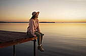 Caucasian woman sitting on dock of lake admiring sunset