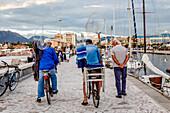 Fishermen going home on the Pier in Viareggio at the Sunset, Viareggio, Tuscany, Italy, Europe