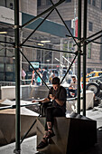 young man sitting and smoking at a construction area in front of Wall Street subway station and staring at his mobile phone, Manhattan, NYC, New York City, United States of America, USA, North America