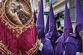 Nazarenos participating in a religious procession, with the traditional robes and hoods and carrying a banner for their brotherhood during Semana Santa (Easter) in Seville.