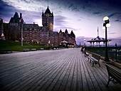 Boardwalk of Dufferin terrace and the Fairmont Le Château Frontenac castle at dusk with dramatic night sky and street lights, luxury grand hotel Chateau Frontenac, National Historic Site of Canada. Old Quebec City, Quebec, Canada. Terrasse Dufferin, Ville