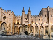 Evening light over the Gothic twin towered facade of the Palais Neuf, Palais des Papes, Palace Square, Avignon, Vaucluse, Provence-Alpes-Cote d'Azur, France.