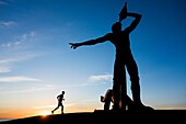 Las Palmas, Gran Canaria, Canary Islands, Spain. A jooger stretches in pre dawn light near sculpture of Greek God, Triton ( son of Poseidon and Amphitrite ) overlooking La Laja beach on the southern outskirts of Las Palmas city.