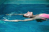 Side view of woman swimming on back in the pool and relaxing with eyes closed. Horizontal indoors shot.