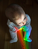 High Angle View of Baby Sitting on Floor with Rainbow