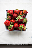 High Angle View of Carton of Fresh Strawberries on White Background