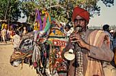 Hippie Flea Market , Flute player with cow at  Anjuna Beach , North Goa, India