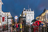 People with umbrellas, Piccadilly circus, rain, evening, Subway entrance, London, UK