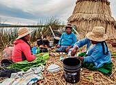 Native Uro Family preparing a meal, Uros Floating Islands, Lake Titicaca, Puno Region, Peru, South America