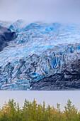 Bright blue ice of Mendenhall Glacier flowing from Juneau Ice Field, mist on Mendenhall Lake, Juneau, Alaska, United States of America, North America