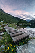 Wood walkway on the shore of Lake Cavloc, Maloja Pass, Bregaglia Valley, Engadine, Canton of Graubunden, Switzerland, Europe