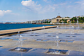 Waterfront view of fountains at umbrellas area, statue of Alexander The Great and city's landmark White Tower, Thessaloniki, Greece, Europe