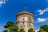 View of the city's landmark The White Tower, with Greek flag waving on top, Thessaloniki, Greece, Europe