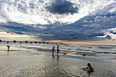 Beach with people and storm clouds of Miedzyzdroje, island Wollin, Baltic Sea coast, Poland