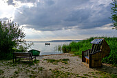 Beach chair with park bench and fishing boat on the shore on the lagoon side in Lieper Winkel, Usedom, Ostseeküste, Mecklenburg-Western Pomerania, Germany