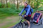 Mother with child trailer biking on a forest path, Usedom, Ostseeküste, Mecklenburg-Vorpommern, Germany