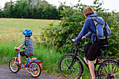Mother with child cycling on a dirt road, Usedom, Ostseeküste, Mecklenburg-Vorpommern, Germany