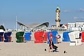 Young woman wearing a headscarf plays soccer on the beach landmark of Warnemünde the Teepott, Ostseeküste, Mecklenburg-Vorpommern, Germany
