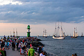 Sailboats in Warnemünde with onlookers and lighthouse to the Hanse Sail, Warnemünde, Rostock, Baltic Sea coast, Mecklenburg-Vorpommern, Germany