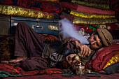 Afghan man smokes opium, Wakhan, Pamir, Afghanistan, Asia