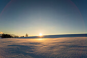 Setting sun behind snowy landscape at the foothill of the bavarian alps, Riegsee, Upper Bavaria, Germany