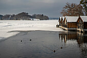Winter at partially frozen Staffelsee with view to the boathouses and the island Wörth with Simpertkapelle (St. Bonifatius), Seehausen, Upper Bavaria, Germany