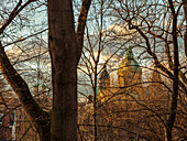 View from the high banks of river Isar through the trees direction inner city on St.Lukas and Frauenkirche, Munich, Upper Bavaria, Germany