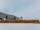 View on snow-covered stacked wood and St.Nikolaus, Unterammergau, Upper Bavaria, Germany
