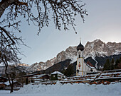 View of the snow-covered cemetery and the parish church of St. John the Baptist in front of the Großer Waxenstein, Grainau, Upper Bavaria, Germany