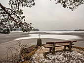 Viewpoint with cross on the shore of the frozen Staffelsee, Seehausen, Upper Bavaria, Germany
