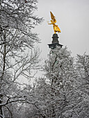 View of the Friedensengel through the snowy trees, Munich, Upper Bavaria, Germany
