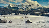 View over snow-covered huts on the frozen Geroldsee and Karwendel mountains, Gerold, Upper Bavaria, Germany