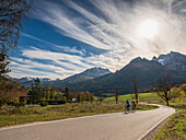 Two cyclists cross the autumn landscape at Watzmann, Ramsau, Upper Bavaria, Germany
