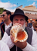 Man blowing conch shell, Romeria de San Benito de Abad, traditional street party, San Cristobal de La Laguna, Tenerife Island, Canary Islands, Spain, Europe