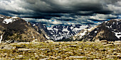 Snow capped mountains and a dramatic cloudy sky in the Rocky Mountain National Park, Colorado.