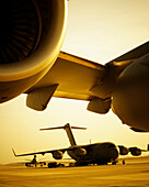 Close up of jet engines with a cargo planes in the background.
