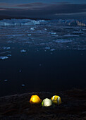 Icy but beautiful night time camping along the shores of the Ilulissat Icefjord in Greenland.  This area is home to some of the world's largest icebergs.