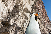A man ice climbing up a frozen waterfall called Cascade Falls in a basin right above the historic downtown of Ouray, Colorado, USA