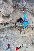 Woman rock climbing cave route called Zero to Hero at Hall of Justice cave, Camp Bird Road, Uncompahgre National Forest, Ouray, Colorado, USA