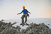 Mountain climber scrambling down steep mixed snow and rock slope on Ashlu Mountain, Coast Mountain Range, Squamish, British Columbia, Canada