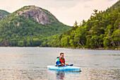 Man kayaking on Jordan Pond in Acadia National Park, Maine, USA