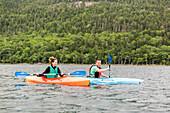 Smiling couple kayaking on Jordan Pond in Acadia National Park, Maine, USA