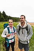 Front view of couple hiking on cloudy morning at Sand Beach in Acadia National Park, Maine, USA