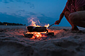 Teenager roasting marsh mellow on beach while kneeling next to small fire in sand, Sheboygan, Wisconsin, USA