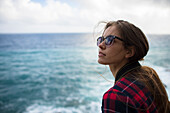 Portrait of woman with brown hair and sunglasses against sea, Sardinia, Italy