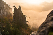 Silhouette of man balancing on highline hanging between two cliffs, Lower Austria, Austria
