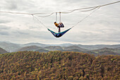 Two athletes performing acroyoga on highline above hills and forest trees, Lower Austria, Austria